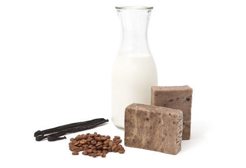 Milk in a glass bottle, coffee beans, soap bars and vanilla beans positioned around.