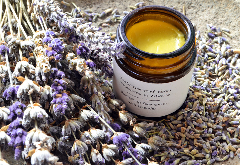 Revitalising face cream jar open and set around lavender flowers and lavender twigs (closeup)