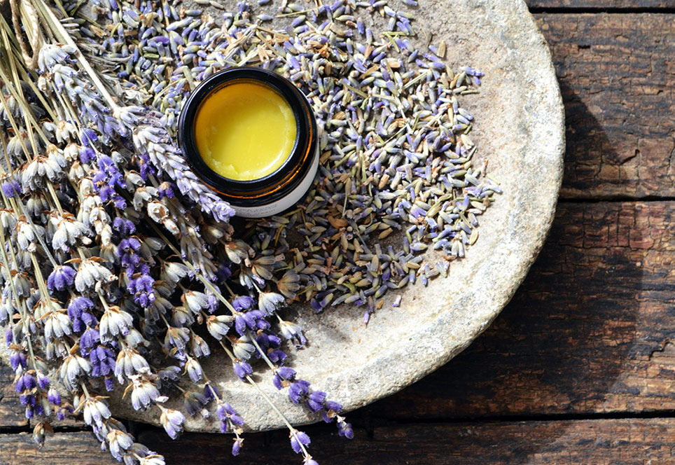 Revitalising face cream jar open and set around lavender flowers and lavender twigs on a gray carved stone plate, on a rustic wooden surface.