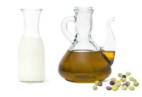 Milk in glass bottle and olive oil in glass jug, and scattered olive fruit.