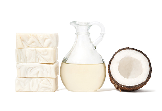 Stacked olive soap bars, half a coconut fruit and coconut oil in a glass jug.
