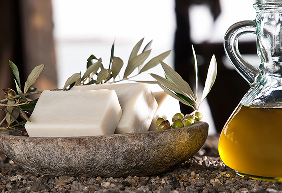 Soap bars lined on a stone bowl, topped with olive branches. Olive oil in a glass jug.