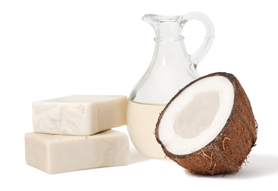 Two soap bars stacked, half a coconut fruit and coconut oil in a glass jug