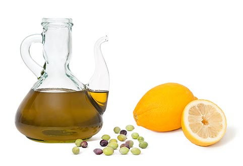 Olive oil in a glass jug, olive fruit scattered and bergamot fruit whole and cut in half