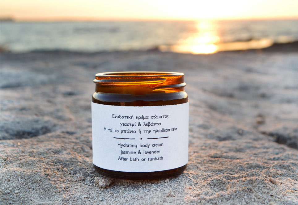 Hydrating body cream jar open and set in front of sunset on a sandy beach